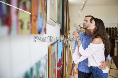 couple looking at paintings in art