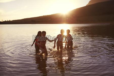 kinder mit freunden geniessen abendschwimmen im