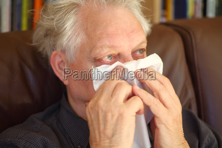 seated senior man blowing his nose