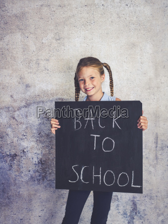blond schoolgirl is holding blackboard with