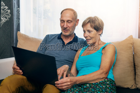 senior couple sitting in sofa and