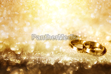 wedding rings on festive golden background