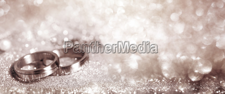 wedding rings on festive silver background