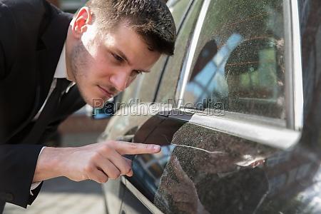 mann inspiziert beschaedigtes auto