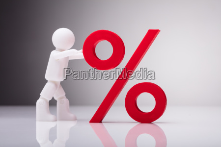 figurine pushing red percentage sign