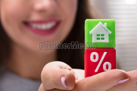 businesswoman holding green and red cubic