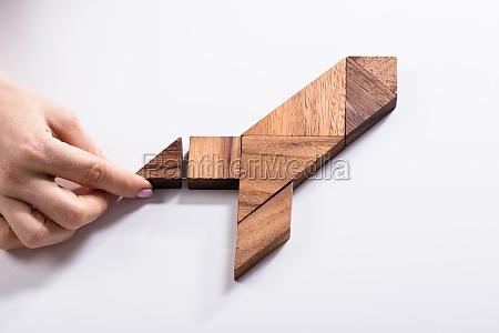 woman making rocket with wooden tangram