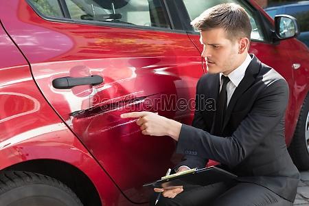 mann fuellt versicherungsformular in der naehe