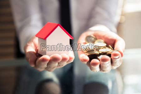 businessperson holding house model and golden