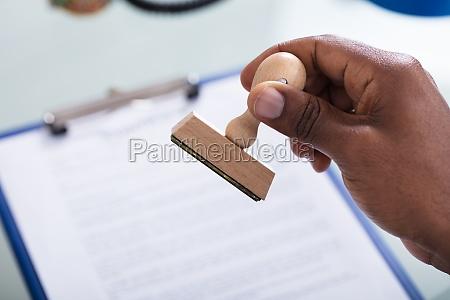hand haelt stempel ueber das dokument