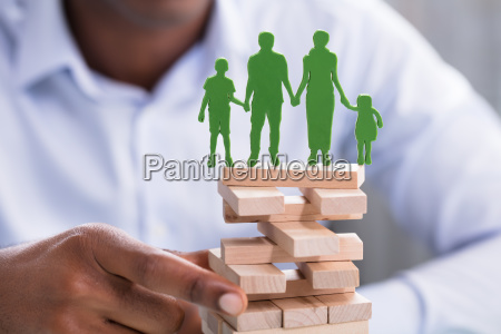 person holding blocks with green family