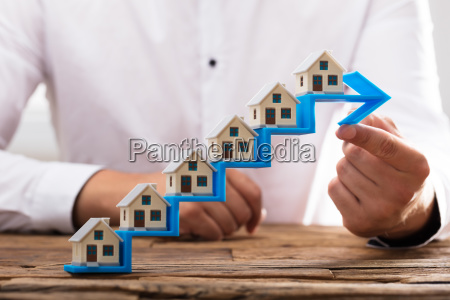 businessman placing house models on increasing