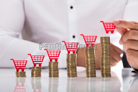 businessperson placing shopping cart over stacked