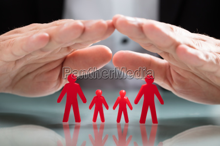 businessperson protecting family figures