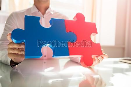 geschaeftsmann der zwei puzzlen anschliesst