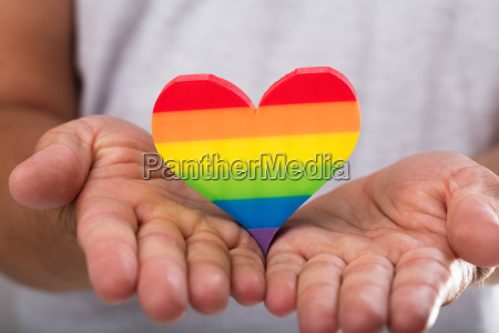 man holding rainbow lgbt heart