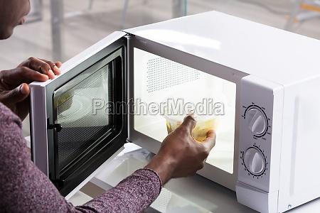 mans hand heating food in microwave