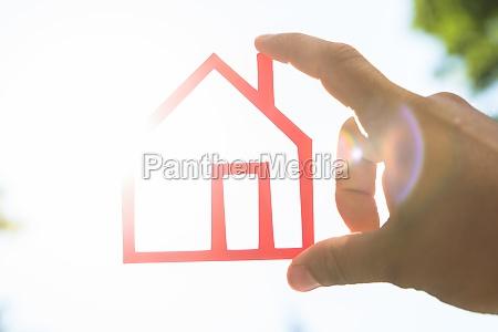 human hand holding house model