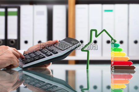 businessman using calculator over reflective desk