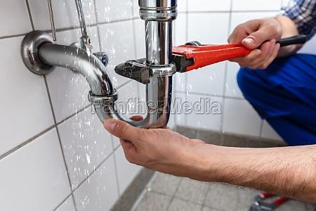 klempner repairing sink pipe leakage