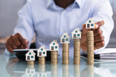 businessperson placing house model on coin