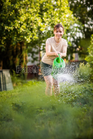 young woman watering plants and flowers