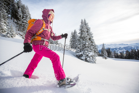 pretty young woman snowshoeing in high