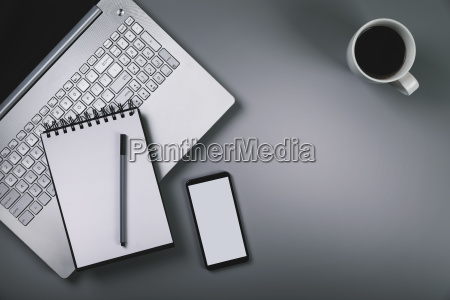 gray desk with laptop smartphone cup