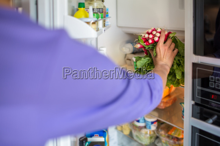 young woman taking fresh vegetable from