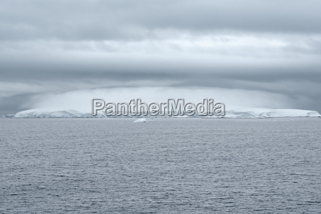 heavy cloud formation above an iceberg