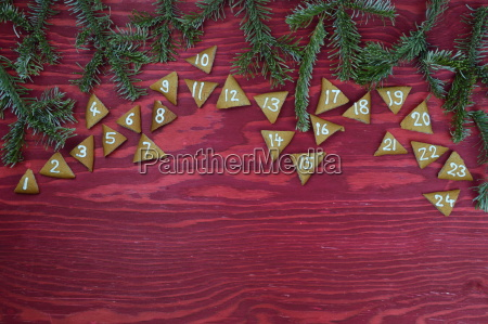 24 adventskekse auf rotem holz mit