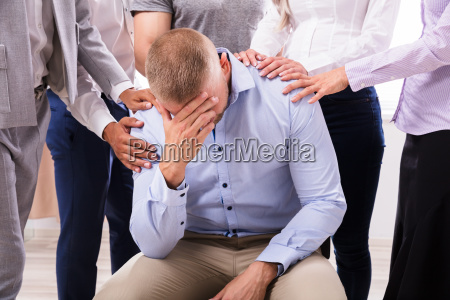 group of people consoling upset man