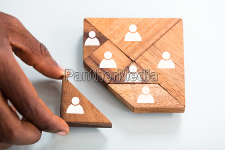 persons hand completing tangram puzzle