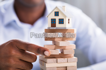 person holding blocks with miniature house