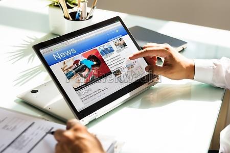 geschaeftsmann checkt online news auf laptop