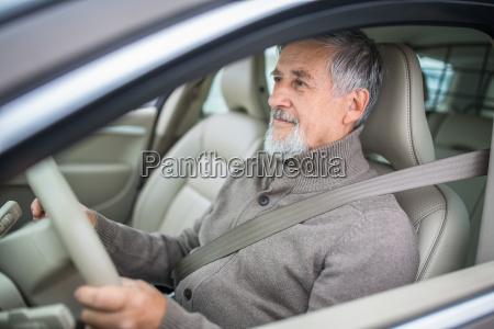 senior man driving his modern car
