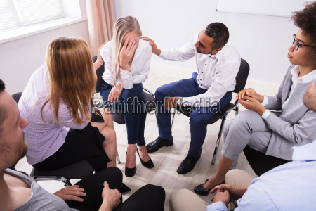 group of people consoling devastated woman