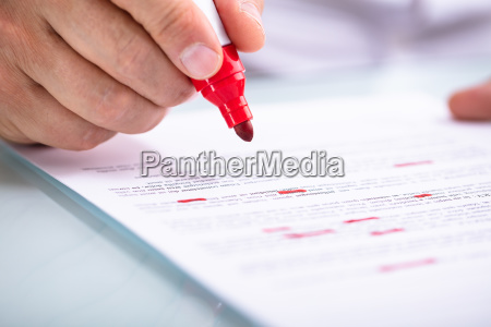 businessperson holding marker on document