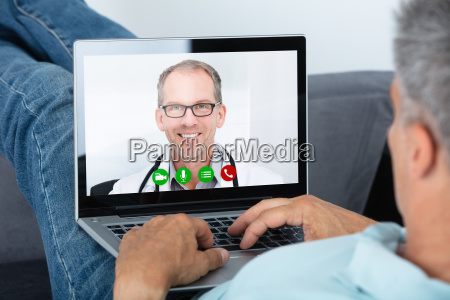 man videoconferencing with doctor on laptop