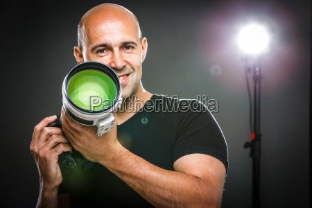 junge professionelle maennliche fotografin in seinem