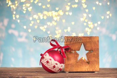 roter weihnachtsball mit hoelzerner laterne auf