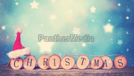 hoelzerne weihnachtsbuchstaben mit rotem sankt hut