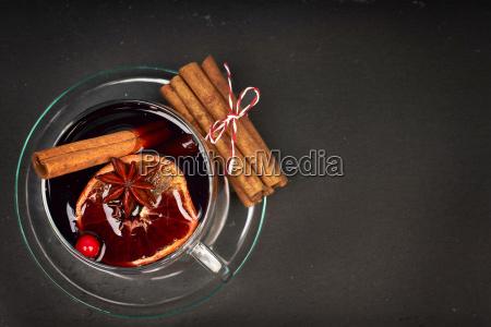 glas gluehwein mit gewuerzen und weihnachtsplaetzchen