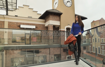 girl stands on the balcony of