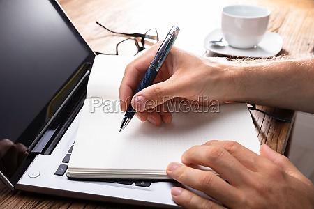 handschrift der person auf schwarzem notebook