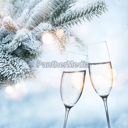 tannenzweige im winter mit champagnerglaesern