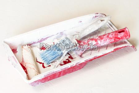 alte farbwalze und lackierpinsel in getrocknetem