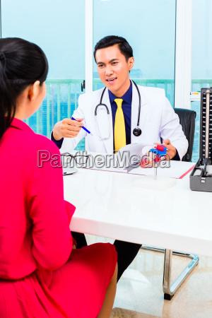 asiatischer arzt mit patient in der