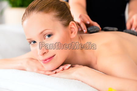 woman having wellness spa hot stone