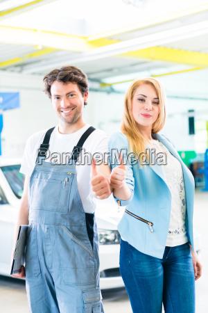 workshop mechanic handing over car to